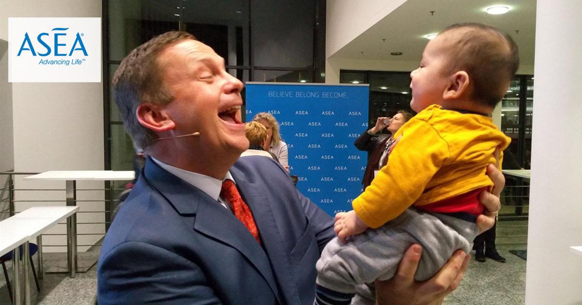 Tyler Norton, fundador de ASEA, sosteniendo un niño durante el evento